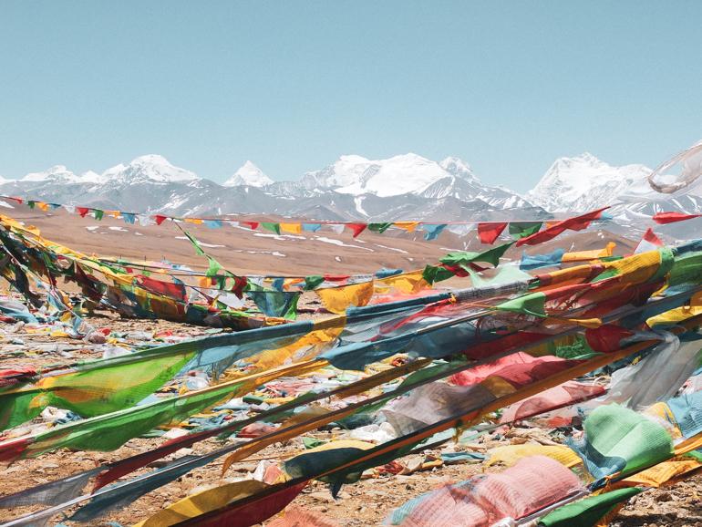 besneeuwde Himalayatoppen en wapperende Tibetaanse gebedsvlaggen