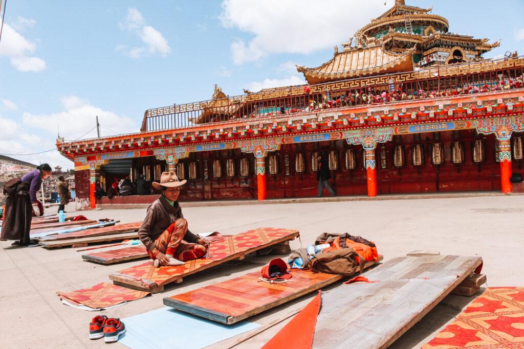 Toegewijde boeddhisten bezig met prostraties bij de hoofdingang van de tempel in Larung Gar Oost Tibet, YourTravelReporter.nl